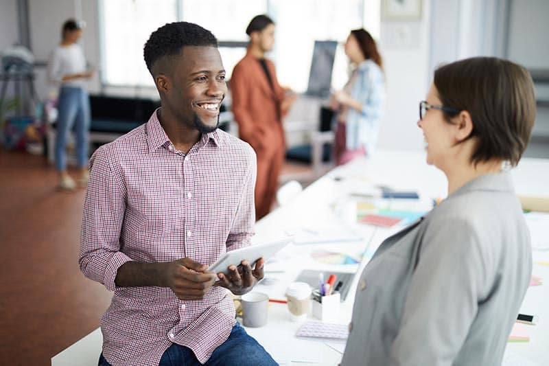 Portrait of smiling African-American man talking to female colleague while chatting casually in modern office, copy space